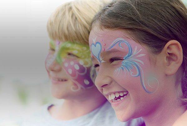 Deux enfants maquillés sur le visage sourient