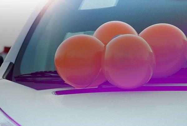 Des ballons de baudruche orange sont attachés en grappe sur le devant d'une voiture