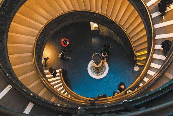 Un escalier en colimaçon avec des personnes qui montent et descendent