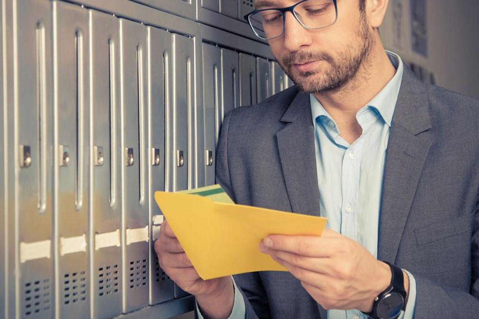 Un homme lit le courrier reçu dans sa boite-à-lettre