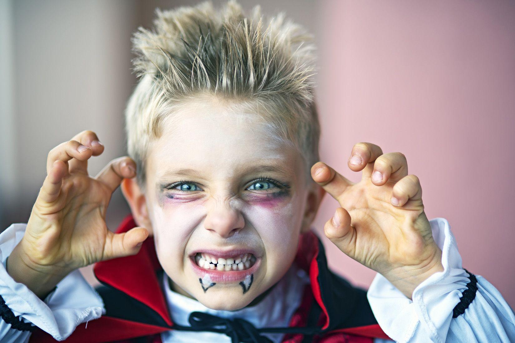 Plan serré d'un enfant maquillé en Dracula faisant une grimace