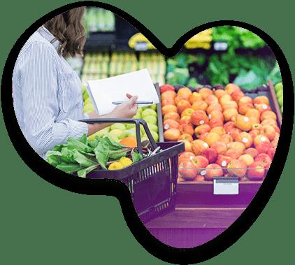 Une cliente tenant son panier de courses dans un rayon fruits et légumes