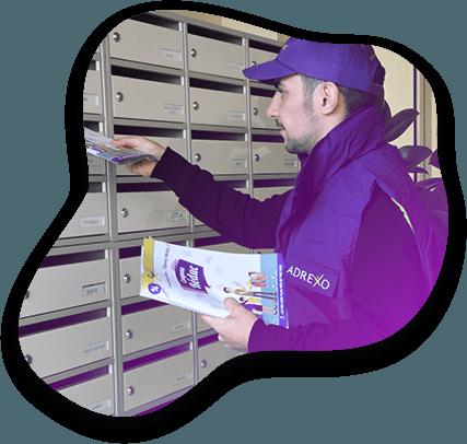 Distributeur Adrexo en train de déposer des prospectus dans une boîte-à-lettres